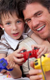 Father and his son playing video games. Excited father and his son playing video games Royalty Free Stock Photo
