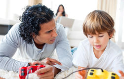 Father and his son playing video games. Lying on the floor in the living-room Stock Photo