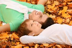 Father and his son resting on fallen leaves. In park royalty free stock photography