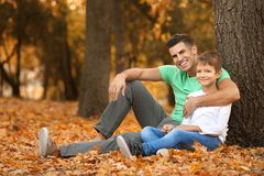 Father and his son resting near tree. In park royalty free stock photo
