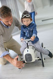 Father with his son riding car toy Royalty Free Stock Images