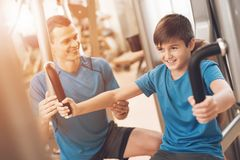 Dad and son in the same clothes in gym. Father and son lead a healthy lifestyle. Father with his son in the same clothes in the gym. Father and son spend time Royalty Free Stock Photography