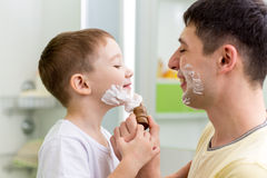 Father and his son shaving and having fun in. Playful father and his son shaving and having fun in bathroom royalty free stock photos