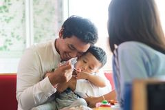 Father and his son sitting and eating cake at indoors cafe. In the morning stock image