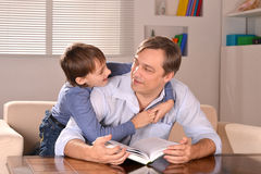 Father and his son sitting on sofa Stock Photos