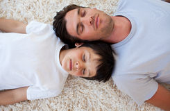Father and his son sleeping on the floor. With heads together royalty free stock photo