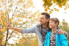 Father and his son spending time together in park. Autumn walk stock photography