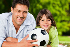 Father and his son with their ball in the park Royalty Free Stock Images