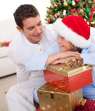 Father and his son unpacking Christmas gifts. Smiling father and his son unpacking Christmas gifts and sitting on the floor royalty free stock photography