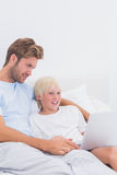 Father and his son using a laptop. In bed stock image