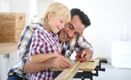 Father and his son working on wood plank Stock Photography