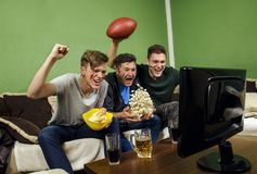 Father and his sons celebrating touchdown. Watching american football / Super Bowl on TV stock images