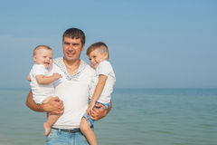 Father and his sons having fun on the beach Royalty Free Stock Image