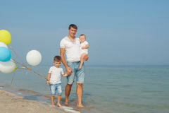 Father and his sons having fun on the beach Stock Photo