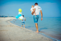 Father and his sons having fun on the beach Stock Images