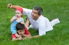 Father and his sons in the park. A father and his sons are playing on the grass in the park Royalty Free Stock Images