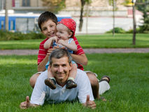 Father and his sons in the park Stock Images
