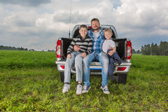 Father with his sons sitting on car trunk Royalty Free Stock Photos
