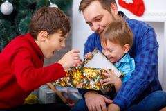 Happy father and his sons at home near the Christmas tree open a gift Stock Photography