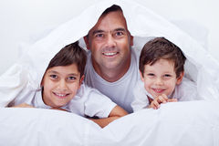Father and his sons spending some lazy time together Royalty Free Stock Photo