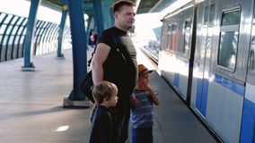 Father with his sons waiting for train. City transport stock footage