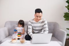 Father and his teenage daughter playing on a portable computer a stock photos