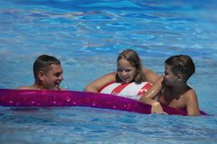 Father and his teenager son and daughter relaxing at the weekend, swimming in a pool on an inflatable pool raft.  stock photography