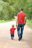 Father and his toddler boy are walking in the park, holding hands. Fatherhood concept. Family look clothing Stock Photography
