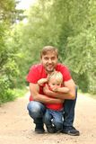 Father and his toddler son fave fun in the summer park. Dad hugging son outdoor. Family look clothing. Copy space Stock Photos