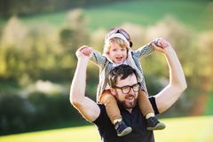 A father with his toddler son outside in spring nature. A father with his toddler son outside in green sunny spring nature, having fun royalty free stock photos