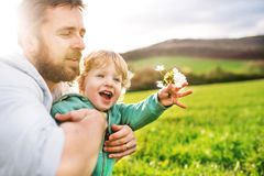 A father with his toddler son outside in spring nature. A father with his toddler son outside in green sunny spring nature stock photos