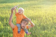 Father and his toddler son playing with toy airplane on summer f. Ield. Childhood or family travel concept. Copy space stock image