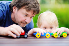Father with his toddler son playing with toy trains. Middle age father with his toddler son playing with toy trains outdoors stock image