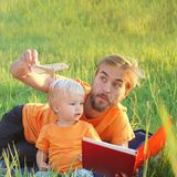 Father and his toddler son read book about airplanes and travel. Authentic family lifestyle image. Copy space.  Stock Photos