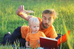 Father and his toddler son read book about airplanes and travel. Authentic lifestyle image. Parenting concept.  Royalty Free Stock Photography