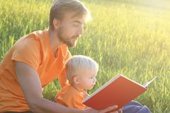 Father and his toddler son read book together outdoor. Copy cpace.  Stock Images