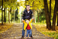 Father and his toddler son walking in autumn forest Royalty Free Stock Photos