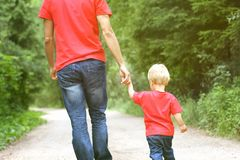 Father and his toddler son are walking in the park, holding hand Stock Photos