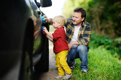 Father with his toddler son washing car together royalty free stock images