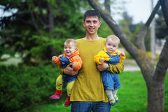 Father with his twins. Portrait of happy young father with his two babies twins outdoor Royalty Free Stock Photo