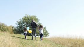 Father with his two daughters with an air balloons running to up on the hill. Happy young family spending time together outside in green nature.Happy family stock video footage