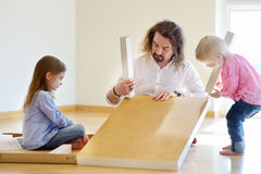 Father and his two daughters assembling a table. Happy father and his two daughters assembling a table together Stock Photos