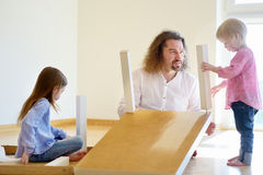 Father and his two daughters assembling a table Stock Photography