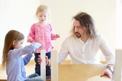 Father and his two daughters assembling a table Stock Images