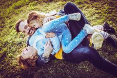 Father with his two daughters. Single father playing with his daughter outdoor on the grass Stock Images