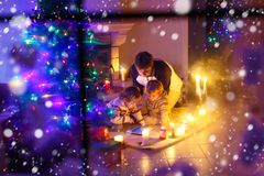 Father and his two little children sitting by fireplace chimney on Christmas Eve time. Dad and kids boys sons playing with tablet. Through window from outdoors stock image