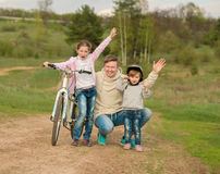 Father and his two little daughters walking with bike Stock Images