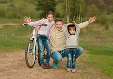 Father and his two little daughters walking with bike Royalty Free Stock Photos