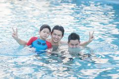 Father and his two son play in clear water stock photography