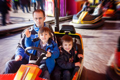 Father and his two sons having a ride in the bumper car at the f Stock Photo